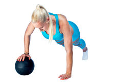 Woman working on push ups with ball Stock Images