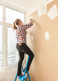 Woman working with putty and spatula on ladder Royalty Free Stock Images