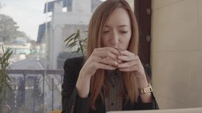 Freelancer worker woman is sitting in cafe with laptop and working, sipping tea stock video
