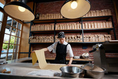 Woman working with rolled knead. Horizontal indoors shot of female cook working with roll of dough for pasta. Making pasta. Making pasta in restaurant Stock Photos
