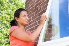 Woman working sanding window outdoors Stock Photo