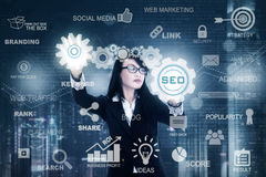 Woman working with SEO icon. Young female entrepreneur working with SEO button on the futuristic screen. Concept of Search Engine Optimization Stock Images