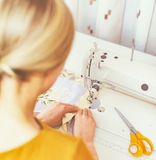 Woman working on sewing machine. Stock Photo