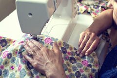 Woman working with a sewing machine. Middle aged woman working with a sewing machine stock photo