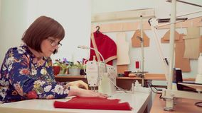 Woman working at the sewing machine in the Studio stock footage