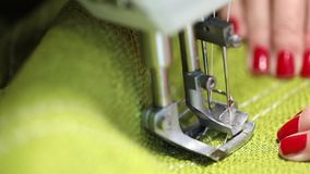 Woman working at a sewing machine, two-needle sewing machine, red manicure on female hands. Slow Motion Video, close-up stock footage