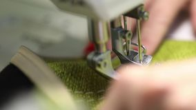 Woman working at a sewing machine, two-needle sewing machine, red manicure on female hands. Slow Motion Video, close-up stock video