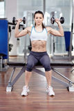 Woman working shoulders with dumbbells Stock Photo
