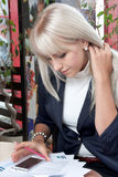 Woman working with a smartphone and business papers Stock Photos