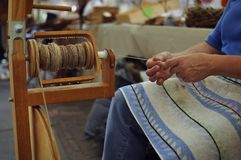 Woman working with the spinning wheel. A woman's hands making yarn with a traditional spinning wheel Royalty Free Stock Photography