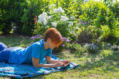 Woman working with tablet outdoors in flowery garden Royalty Free Stock Image