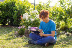 Woman working with tablet outdoors in flowery garden Stock Image