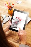 Woman working on tablet. Woman working with tablet placed on wooden desk. Concept of internet shopping Stock Image