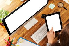 Woman working on tablet. Woman working with tablet placed on wooden desk. Shot from aerial view Stock Image
