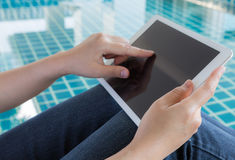 Woman working with tablet sitting at swimming pool Stock Photo