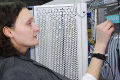 Woman working on telecommunication equipment Stock Images