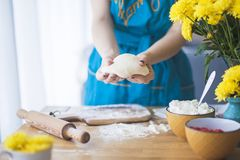 The woman is working with the test, on the table lies a rolling pin and flour royalty free stock images