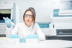 Woman working with test tubes in the laboratory. Young female laboratory assistant in uniform and protective glasses working with test tubes in the medical Stock Photo