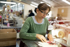 Woman working in textile industry Stock Images