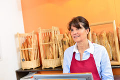 Woman working on till in bakery. Woman working on the till in a bakery Stock Photography