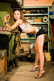Woman working with tools. Woman in dirty t-shirt working with tools in garage royalty free stock images