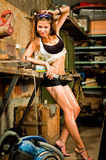 Woman working with tools. Woman in dirty t-shirt working with tools in garage stock photography