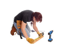 Woman working with tools. A middle age woman kneeling on the floor and working with some tools measuring, isolated for white background royalty free stock photos