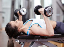 Woman working triceps and chest with dumbbells. Young woman bench pressing with dumbbells in the gym, working triceps and chest stock images