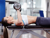 Woman working triceps and chest with dumbbells Royalty Free Stock Image