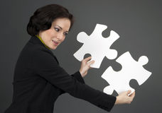 Woman Working With Two Large Jigsaw Puzzle Pieces Royalty Free Stock Photography