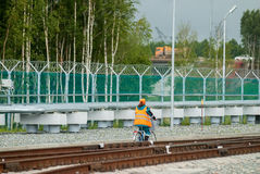 Woman in working uniform goes by bicycle. Tobolsk, Russia - July 15. 2016: Sibur company. Woman in working uniform goes by bicycle stock images