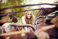 Woman working on vinatge truck. A pretty blond woman leaning into exposed engine of an old truck Stock Photo