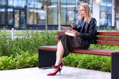 Free Woman Working With Tablet Pc And Smartphone Sitting On A Bench In A Park Royalty Free Stock Image - 198162076