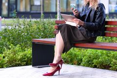 Free Woman Working With Tablet Pc And Smartphone Sitting On A Bench In A Park Stock Images - 198309024