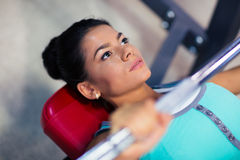 Woman workout with barbell on the bench Stock Photography