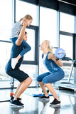 Woman workout with barbell while man having fun with daughter on his shoulders Stock Photos