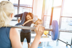 Woman workout with barbell while man having fun with daughter on his shoulders Royalty Free Stock Photos