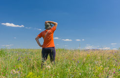 Woman in workout clothes admires summer wild field Royalty Free Stock Image