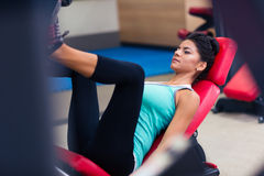 Woman workout on exercises machine at fitness gym Stock Photos