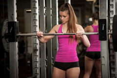Woman workout in fitness gym with barbells - powerlift workout Stock Photos