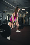 Woman workout in fitness gym with barbells - powerlift workout Royalty Free Stock Image