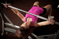 Woman workout in fitness gym with barbells - powerlift workout.  stock photography