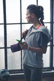 Woman in workout gear holding phone and yoga mat in loft gym Stock Photo