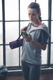 Woman in workout gear in loft gym checking mobile phone Royalty Free Stock Photo