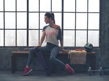 Woman in workout gear posing in profile on loft gym bench Royalty Free Stock Photos