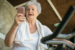 Woman workout in gym. Woman using smart phone on the elli Royalty Free Stock Images