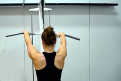Woman workout her back muscles and arms. Woman workout her back muscles and arms with lat pulldown exercise machine at the gym Royalty Free Stock Images