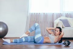Woman workout at home, her sit up stock photography