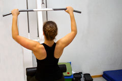 Woman workout with lat pulldown at the gym. Royalty Free Stock Images