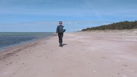 Woman with workout mat walking near sea in windy day. In summer day stock video footage